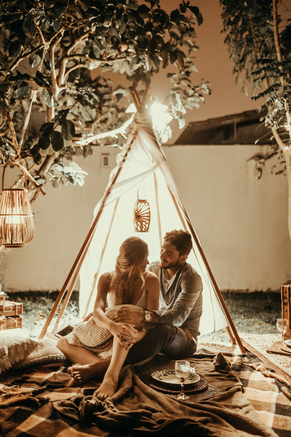 couple sitting inside tepee hut with lights
