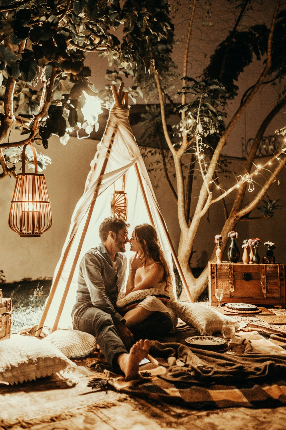 smiling man and woman inside tipi tent