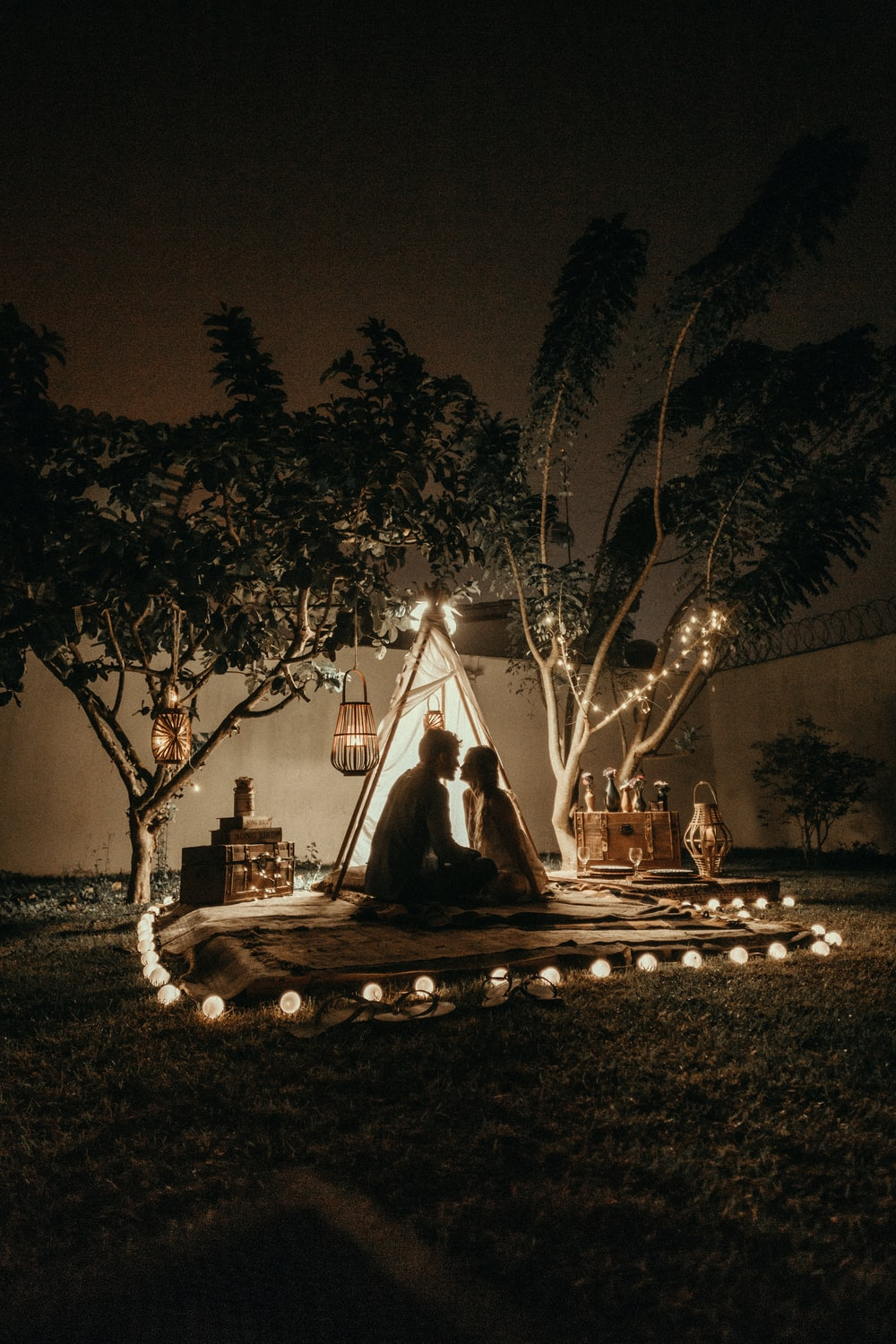 man and woman sitting down on brown carpet near tent surrounded by lights