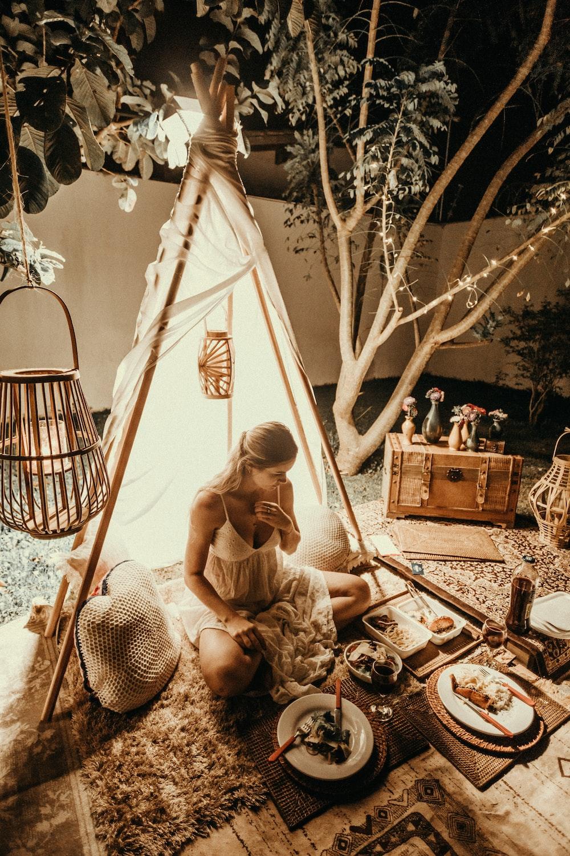 woman sitting under white hut inside room