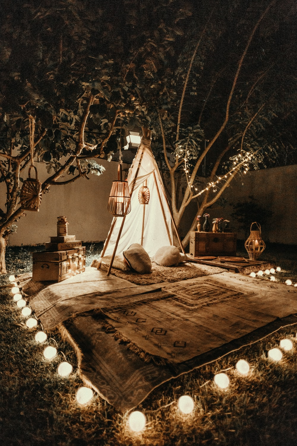 white and brown tipi tent beside trees