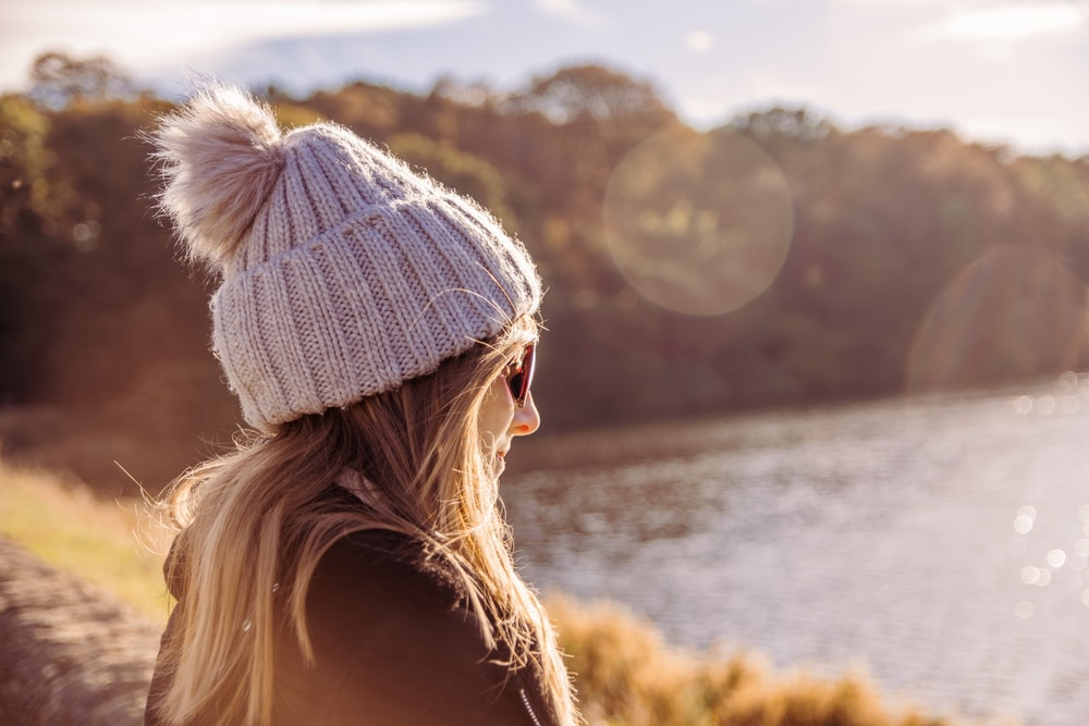 woman wearing jacket looking at body of water