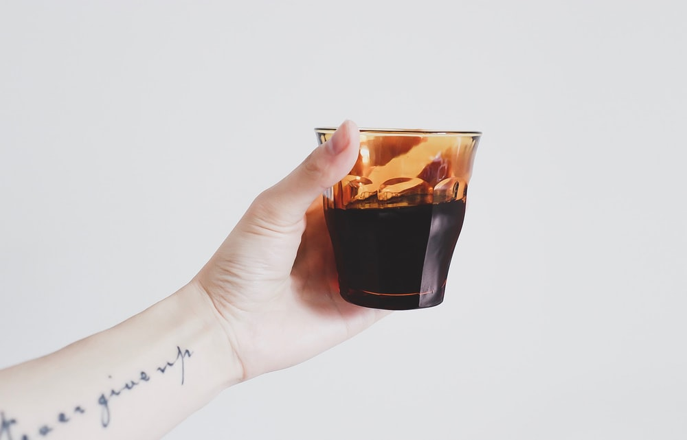 person holding almost full glass cup