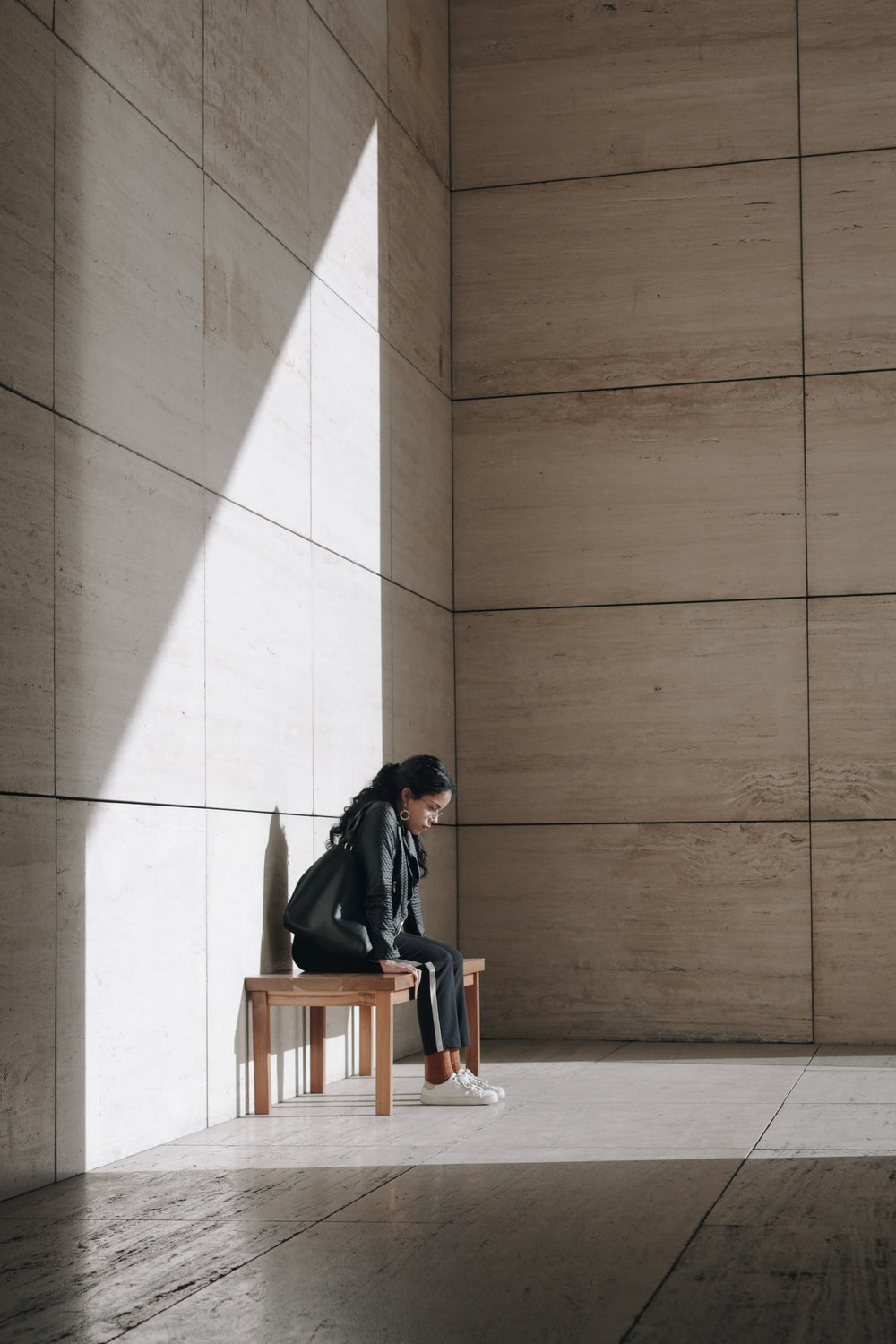 woman sitting alone behind walls