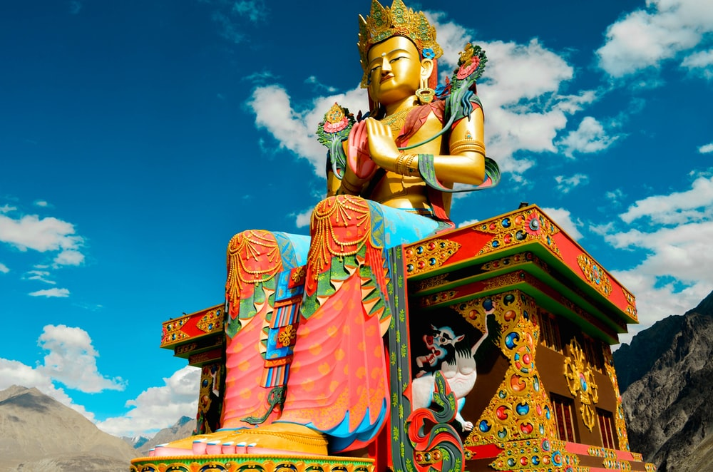 low angle photography of sitting Buddha statue under blue sky and white clouds at daytime