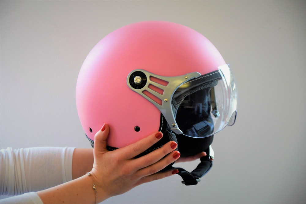 person holding pink helmety