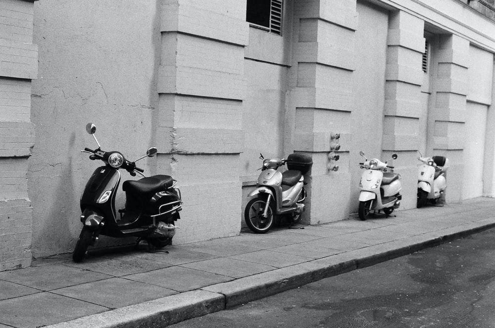 grayscale photography of four motor scooter park beside concrete wall
