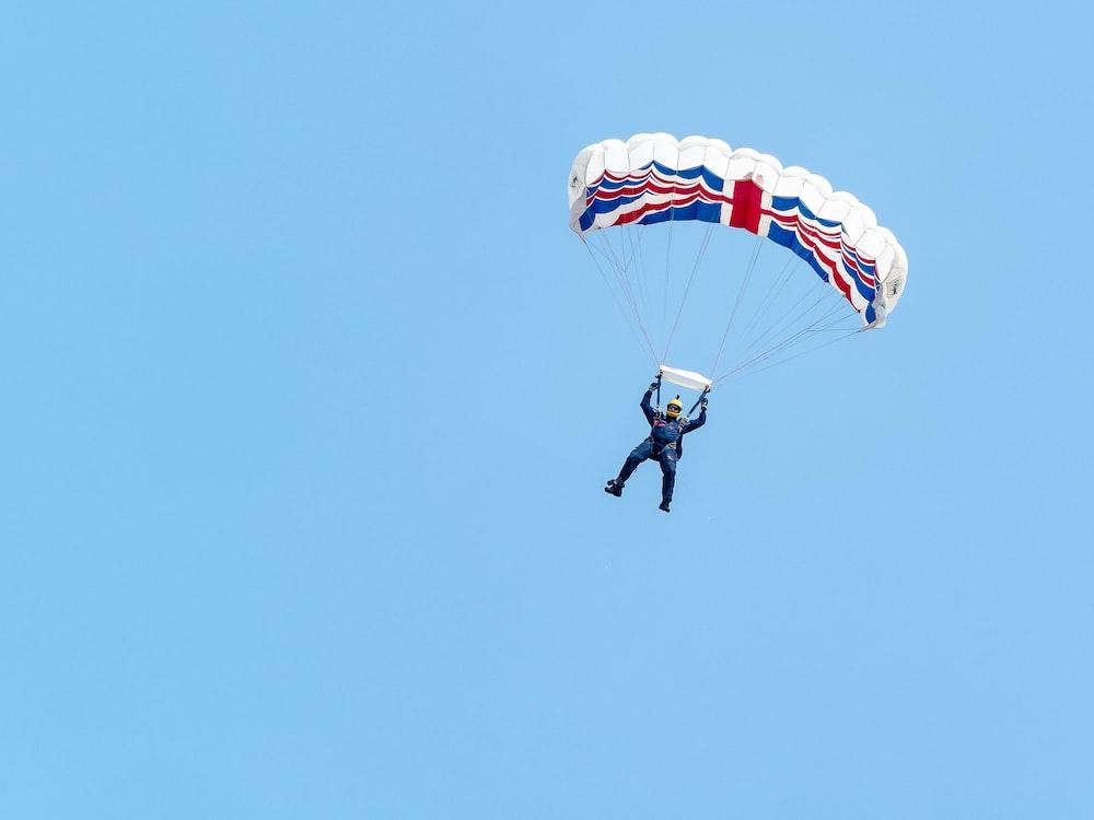 person paragliding under blue sky