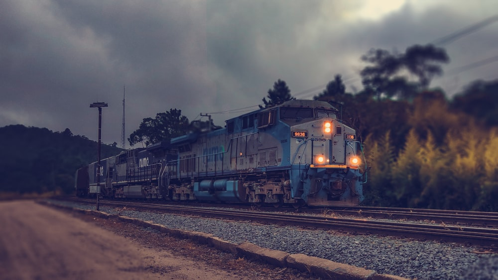 selective focus photography of gray and blue train passing by under cloudy sky