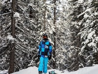 person wearing black ski masks standing near snow covered trees