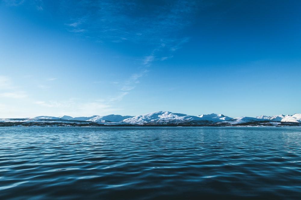 blue calm water near mountains
