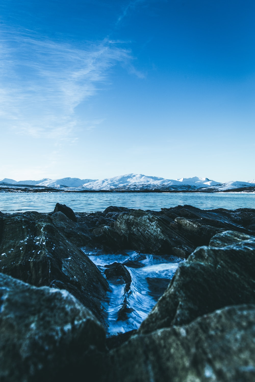 rocks near body of water under blue sky during daytime