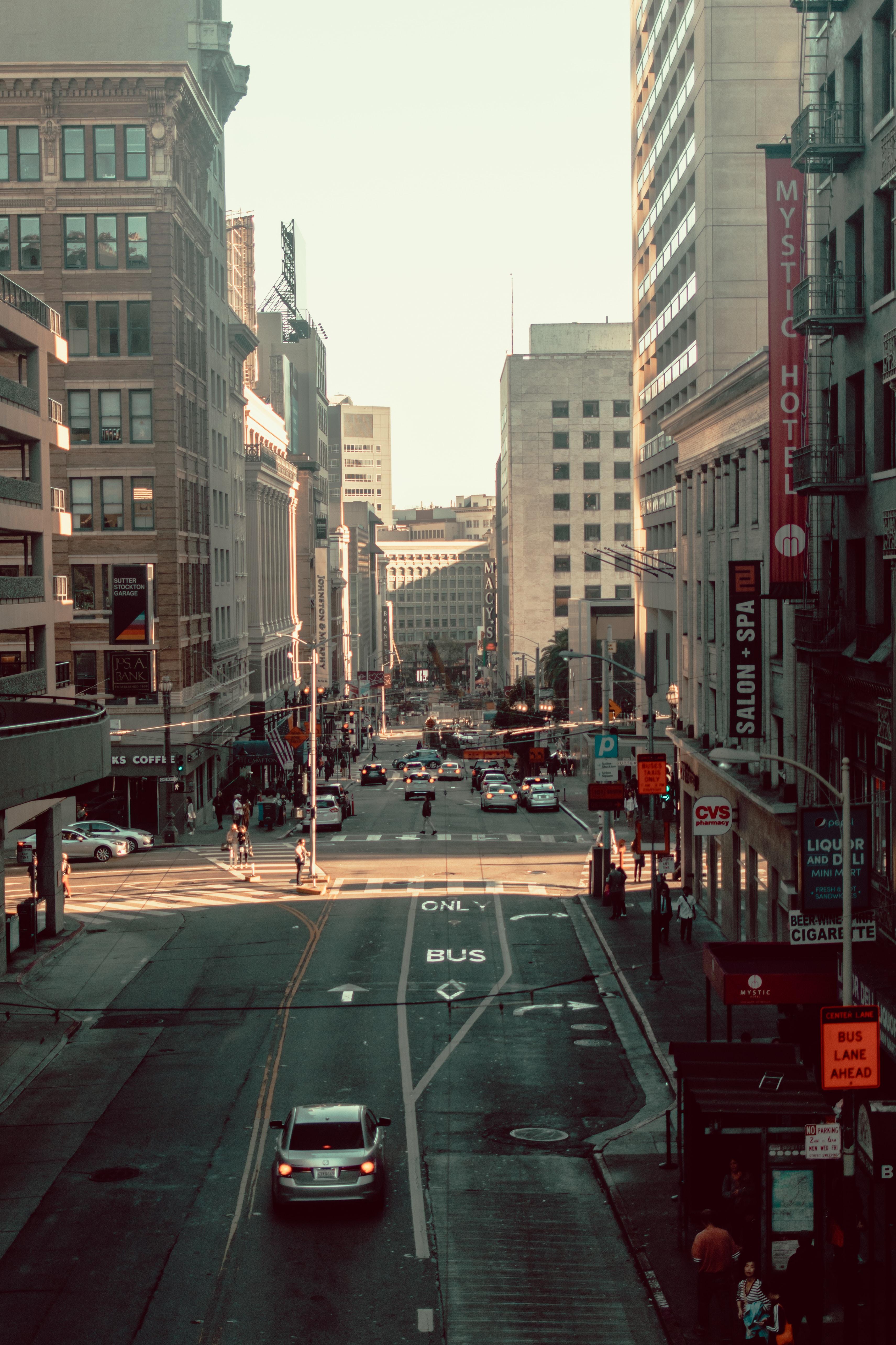 vehicles between buildings during daytime