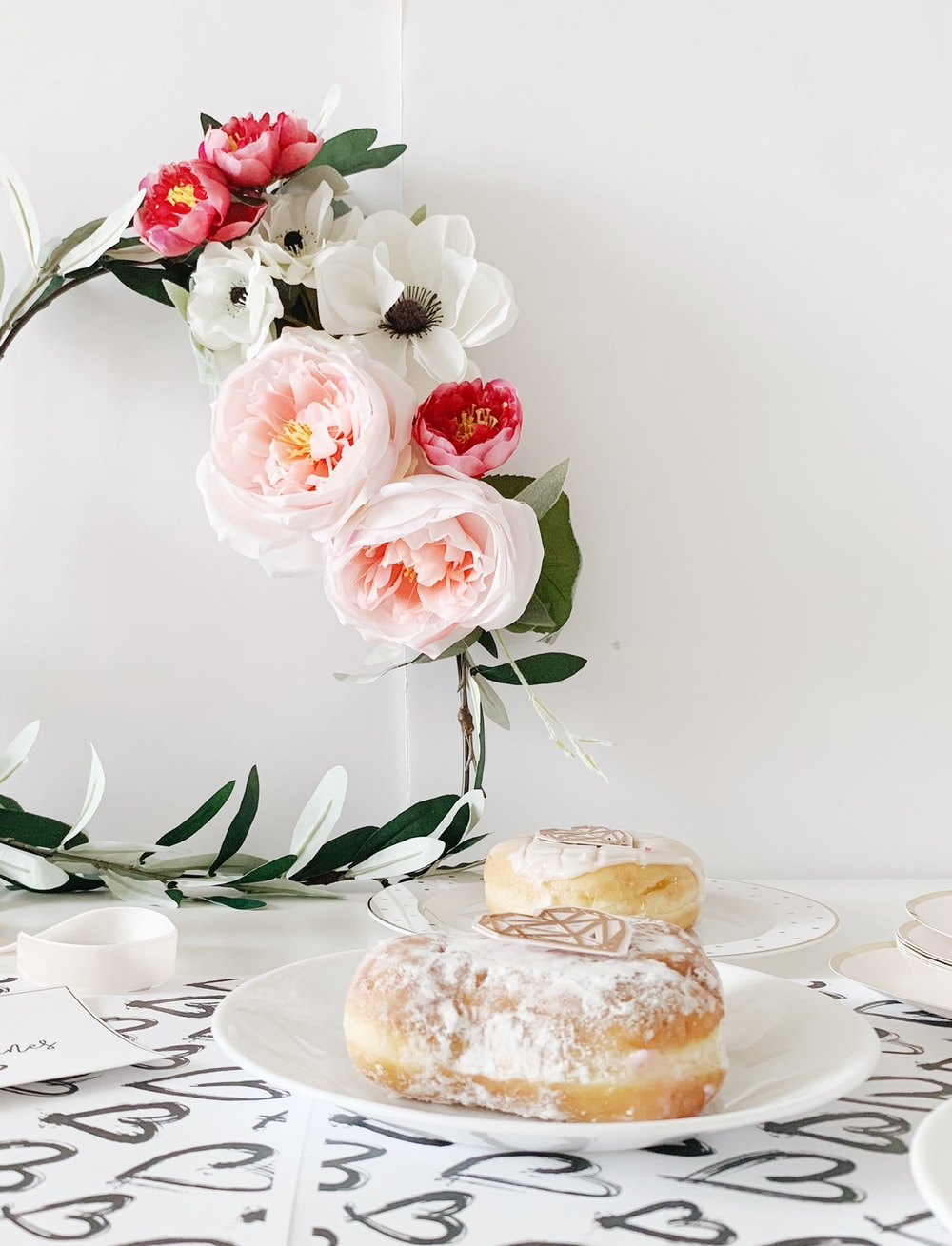 two doughtnuts on white ceramic plates beside petaled flowers