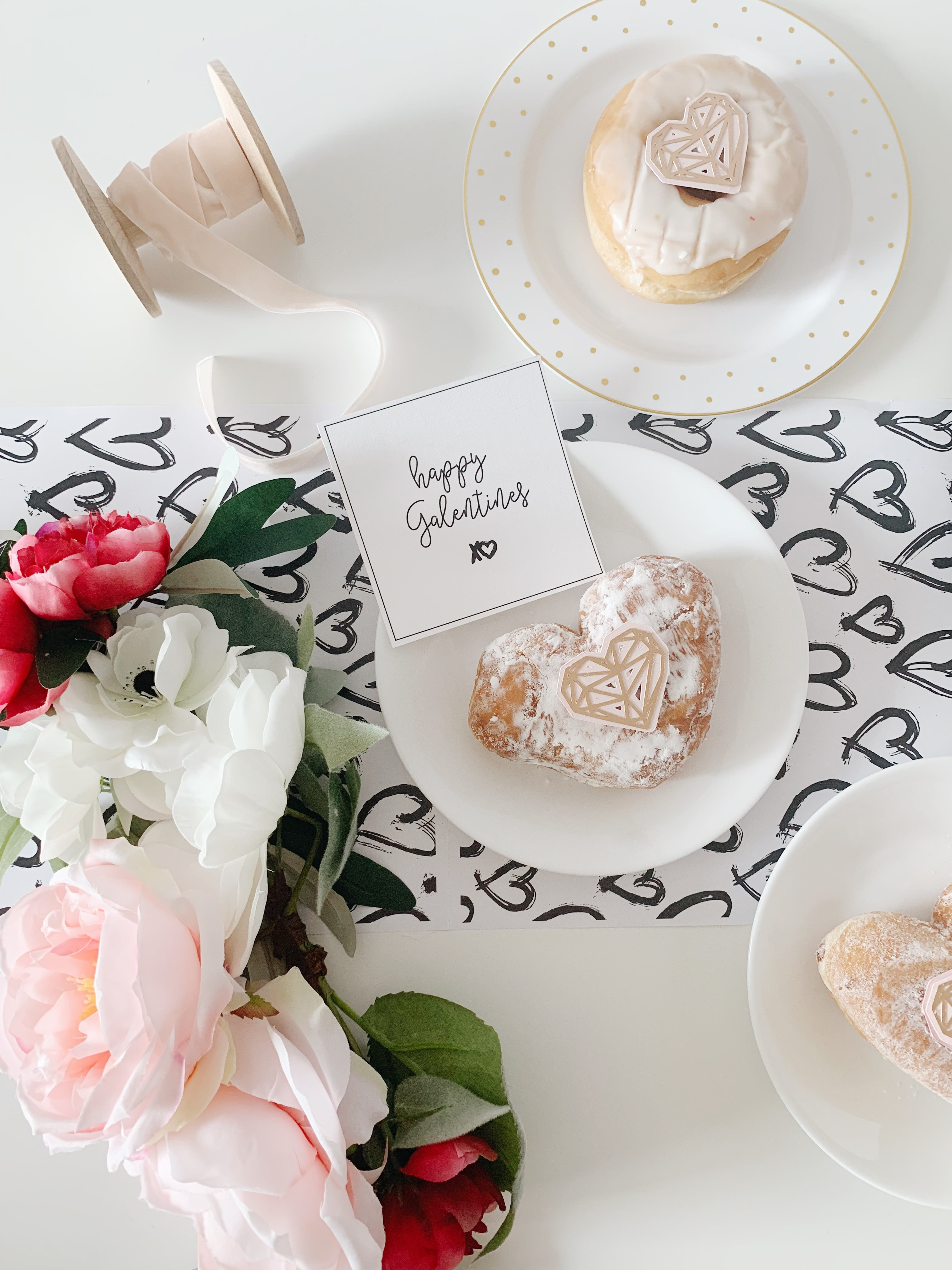 heart doughnut with powdered sugar on white plate