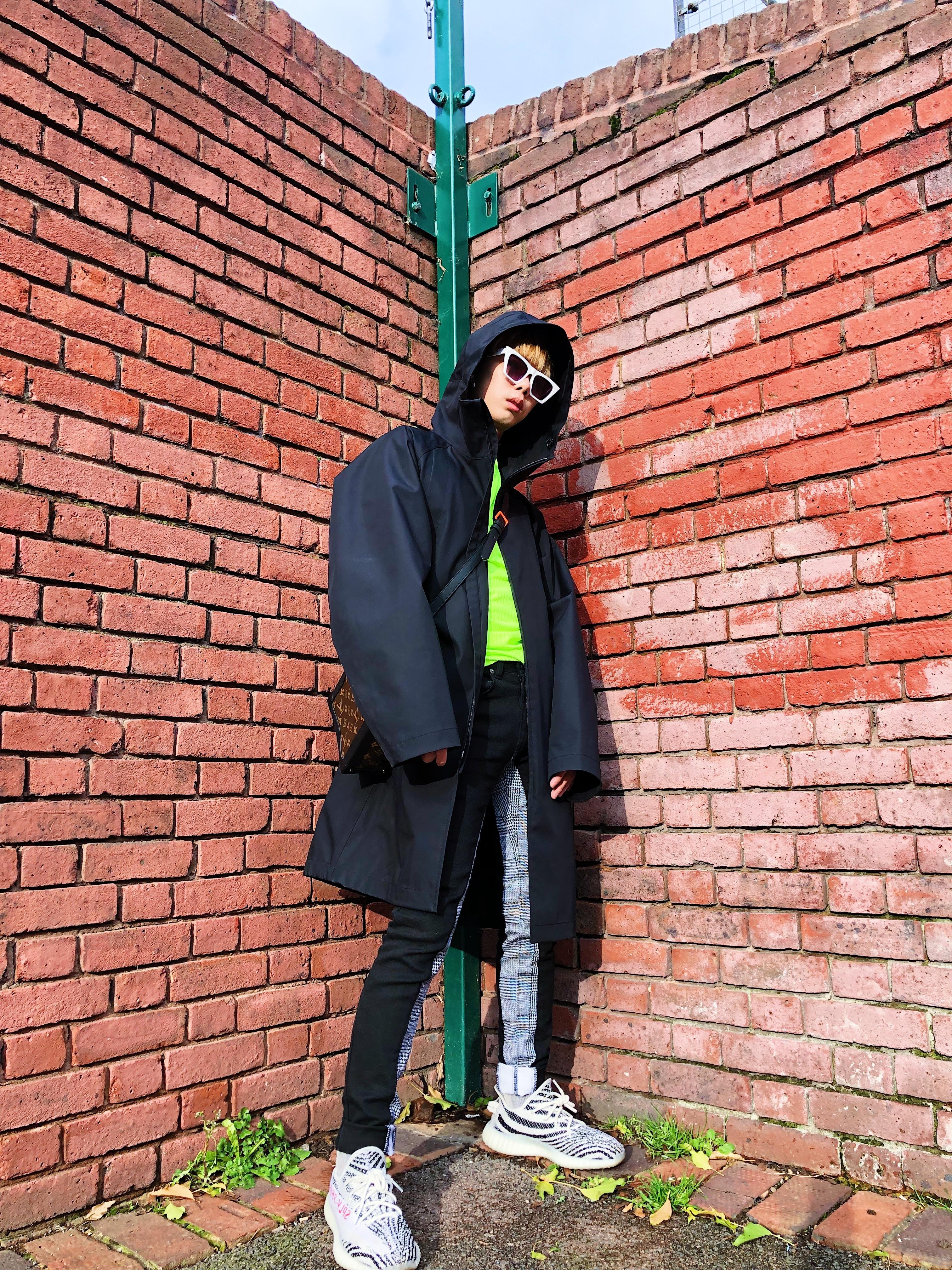man standing behind bricks wall