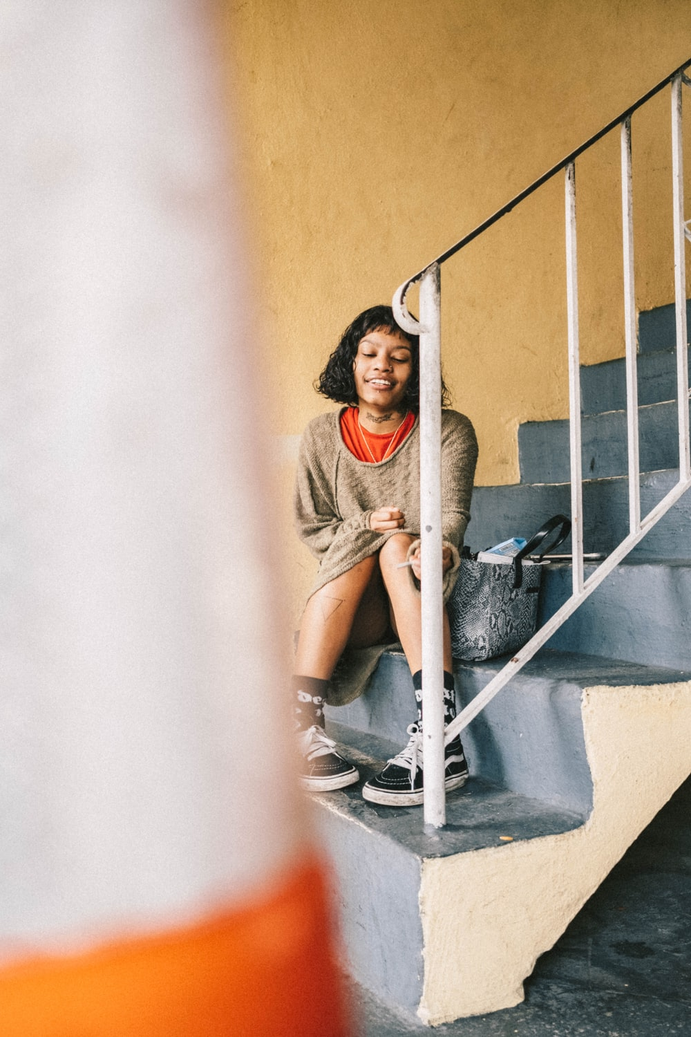 woman sitting on gray concrete stairs \]