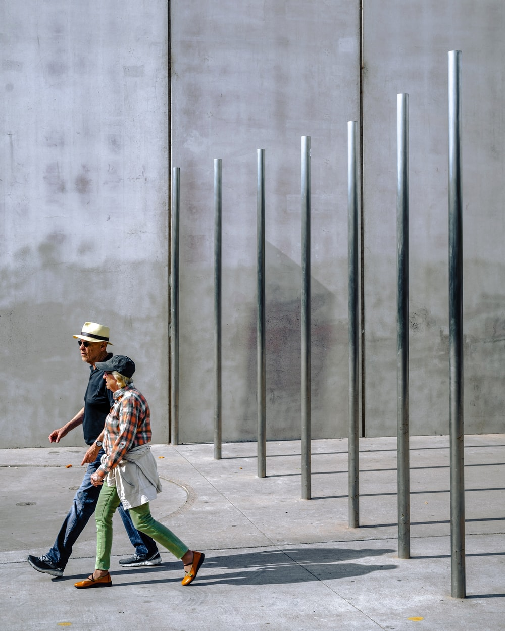 man and woman walking near stainless steel posts