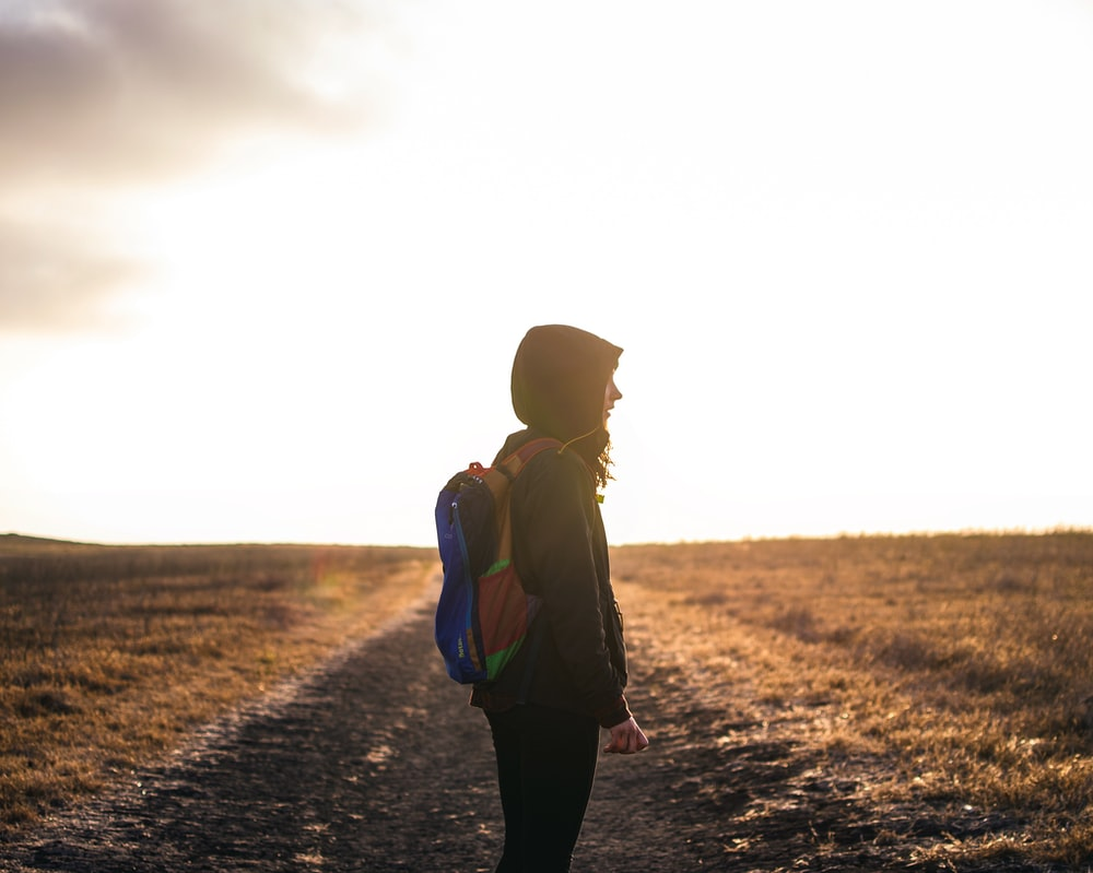 person wearing backpack standing on pathway during golden hour