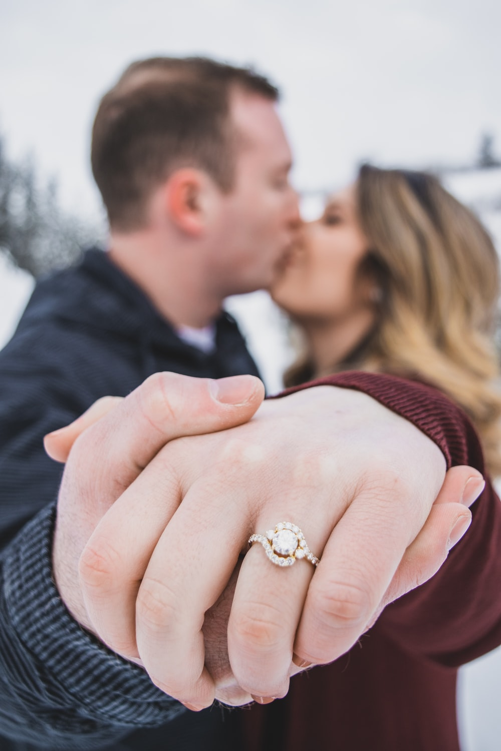 man kissing woman showing her ring
