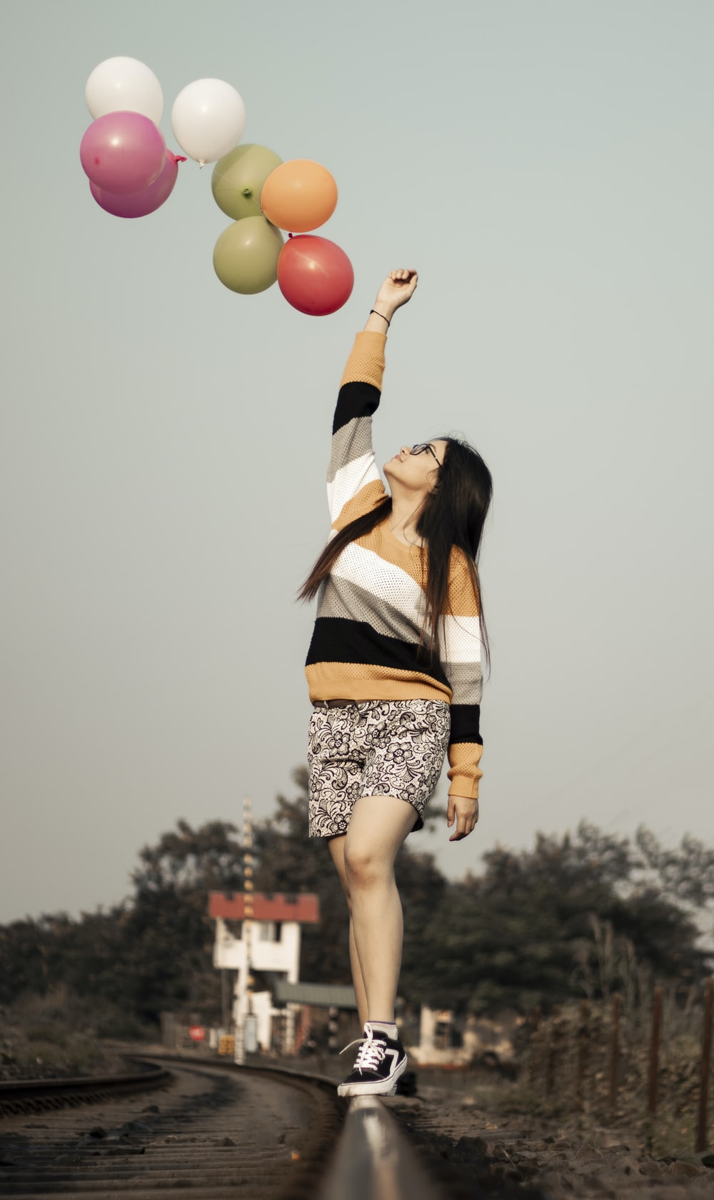 woman on the top of a railway and multicolored balloons