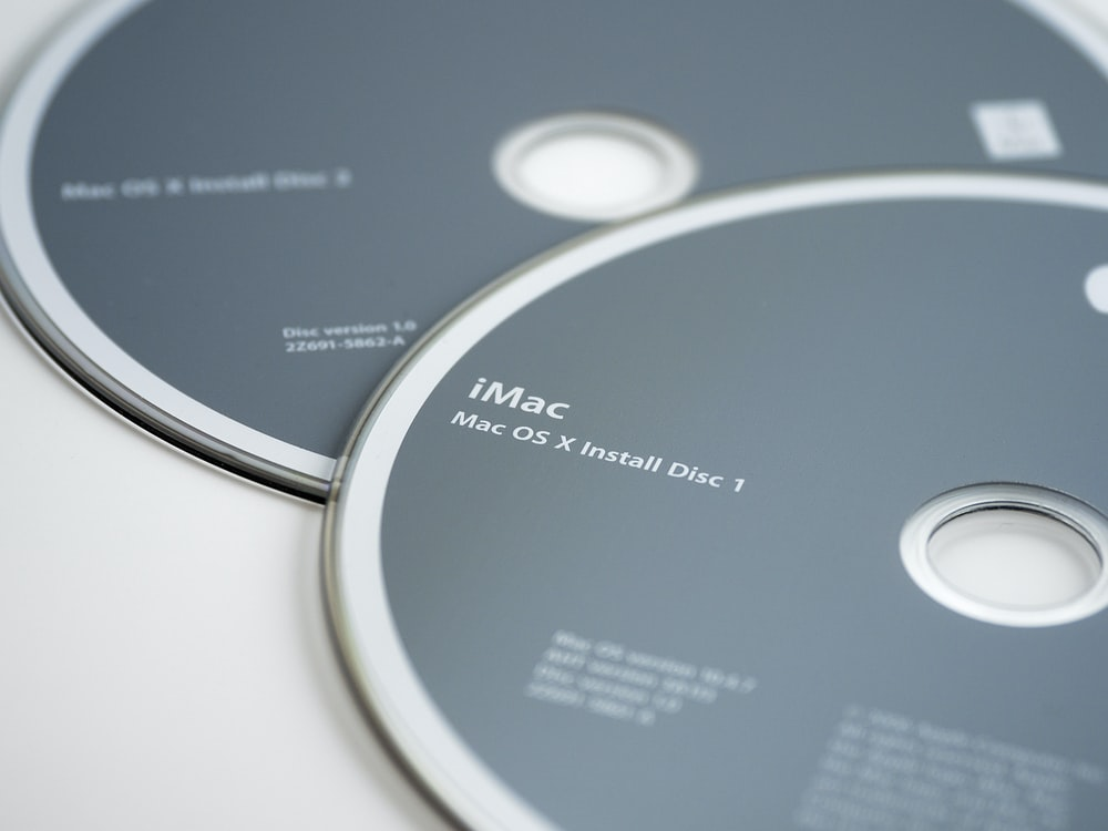 iMac Mac OS X Install Disc 1 and 2 on table