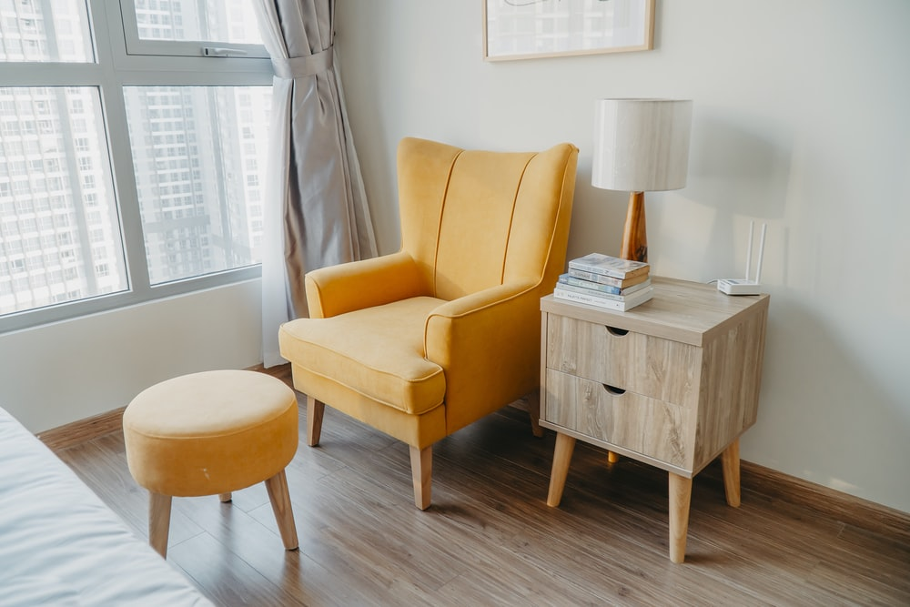 yellow armchair and stool beside wooden nightstand by the wall near glass window and bed