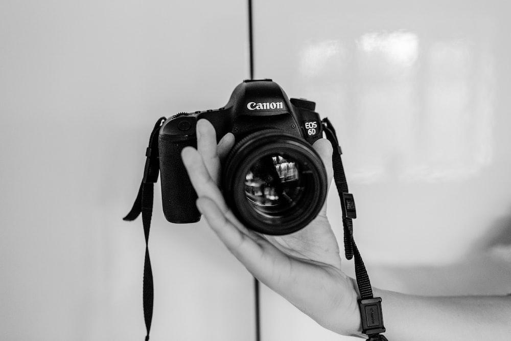 person holding black Canon EOS camera