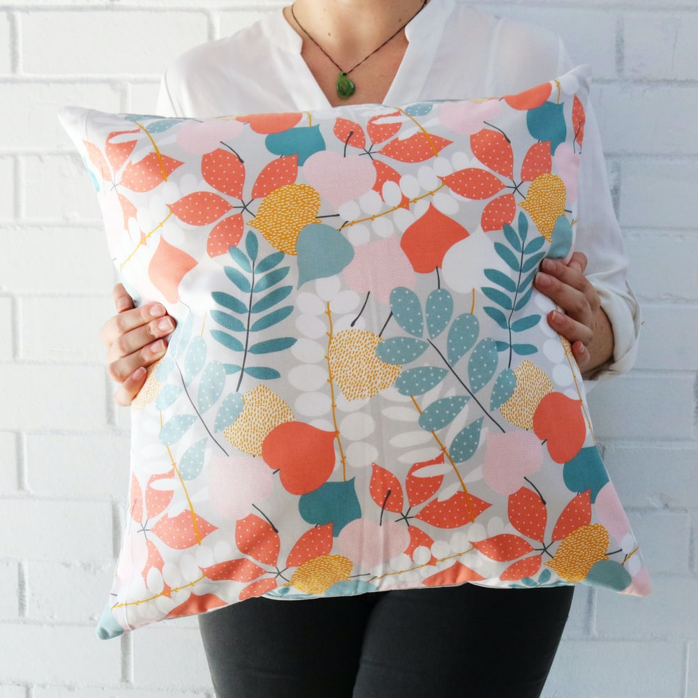 woman holding multicolored floral throw pillow