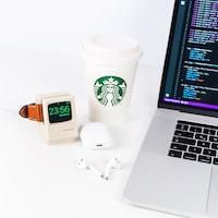 white smartwatch beside Starbucks cup near laptop