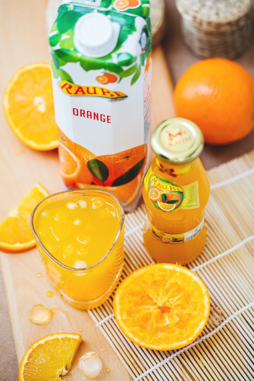 orange juice in glass beside container