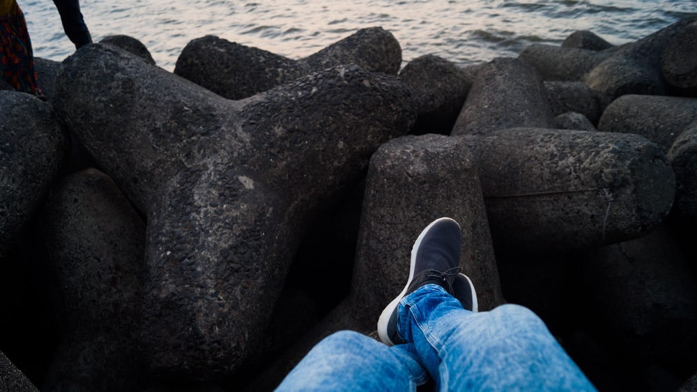 person in blue denim jeans sitting infront of sea