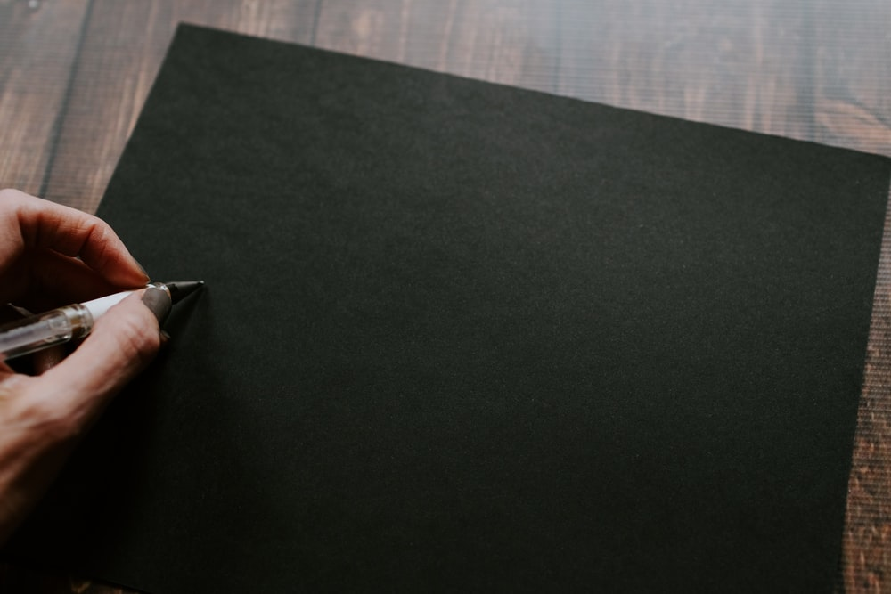 person about to write on empty black sheet