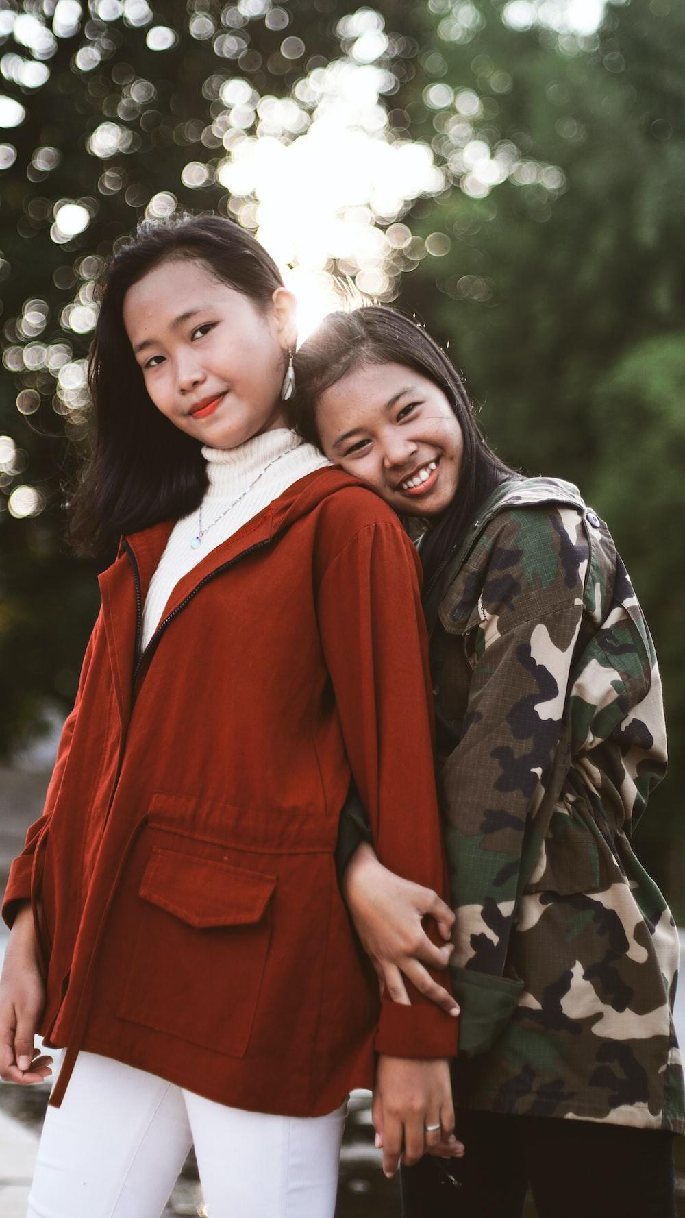 two woman wearing jackets