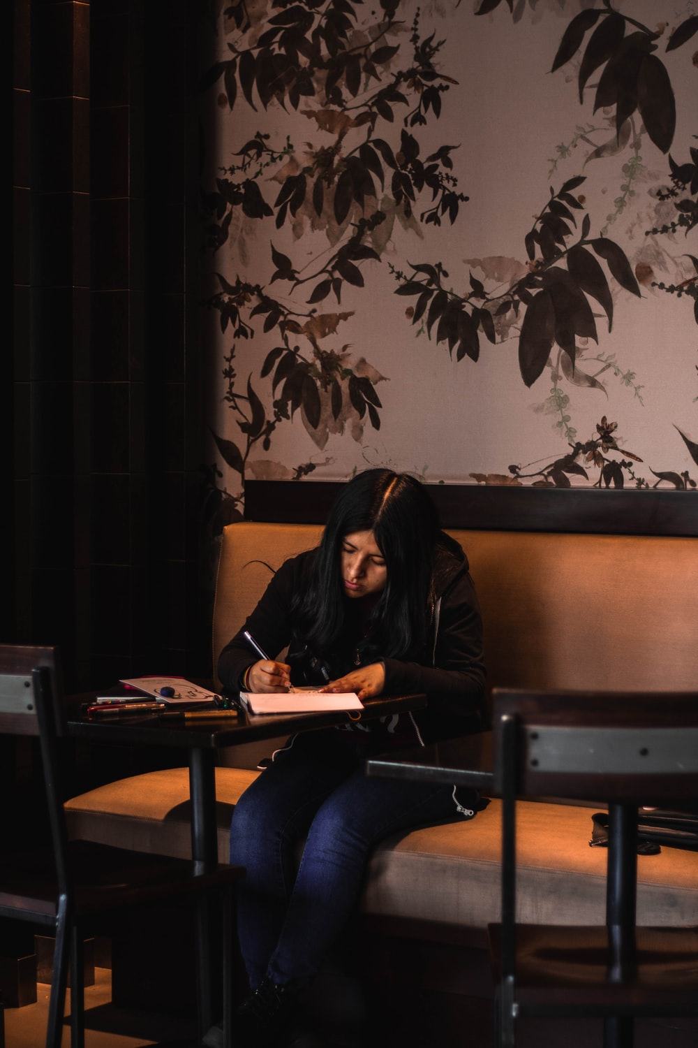 woman writing on white paper while sitting on chair