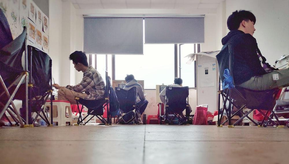 men sitting of chair inside room