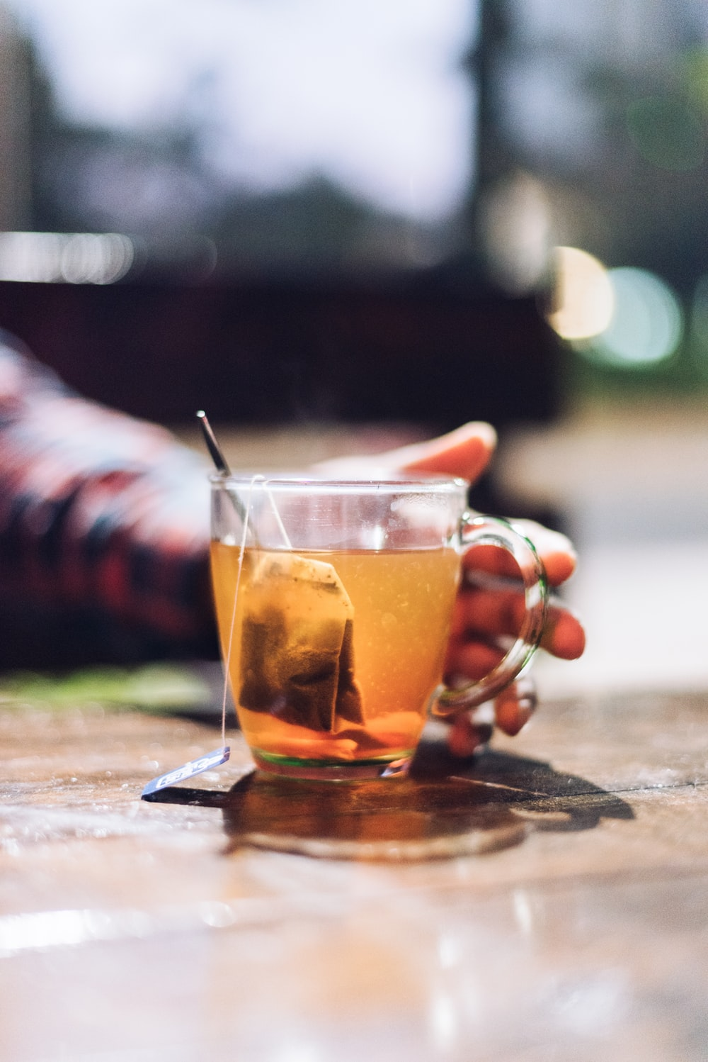 selective focus photography of man reaching for filled glass teacup