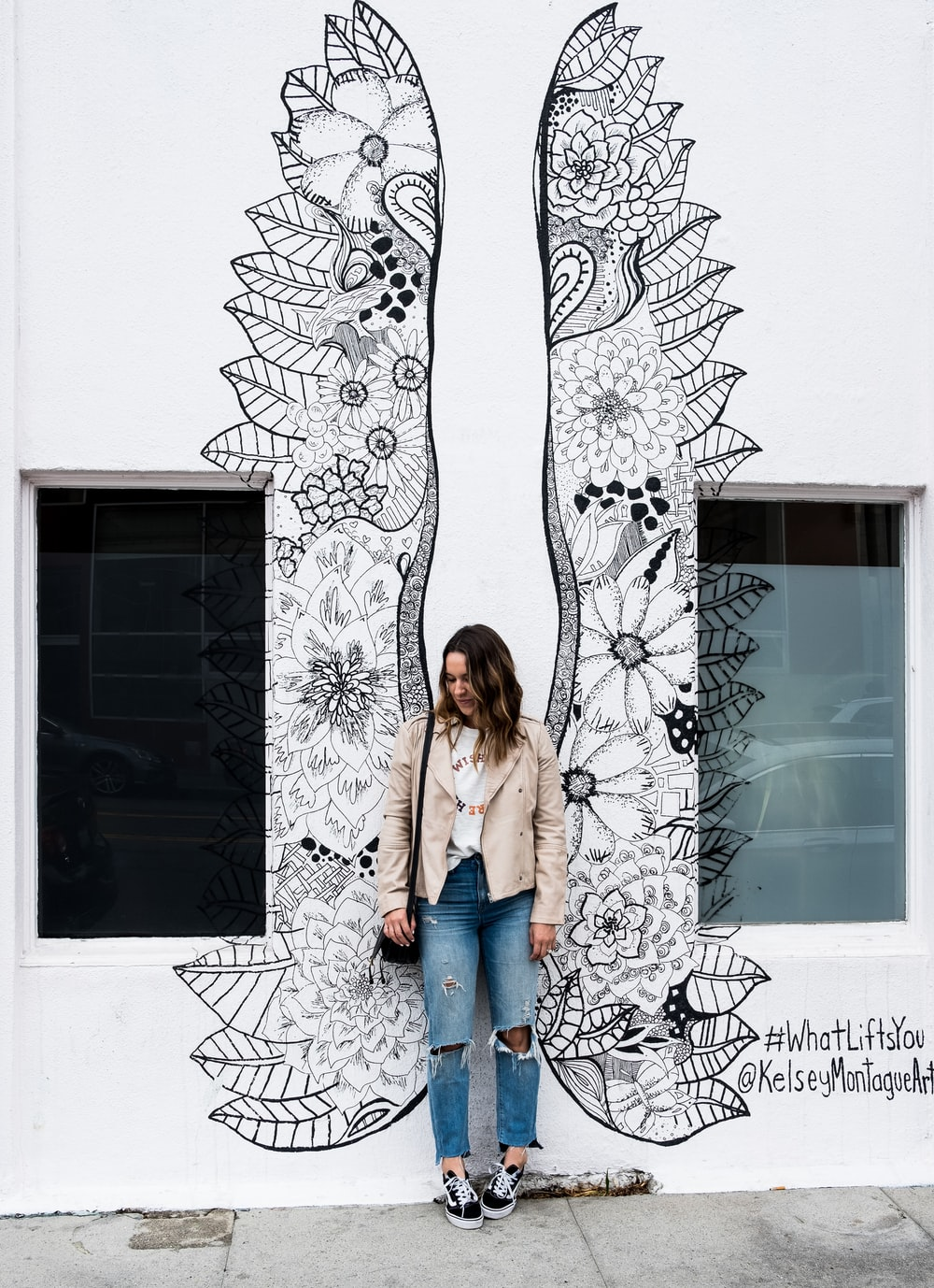 woman standing near wall with wings painting