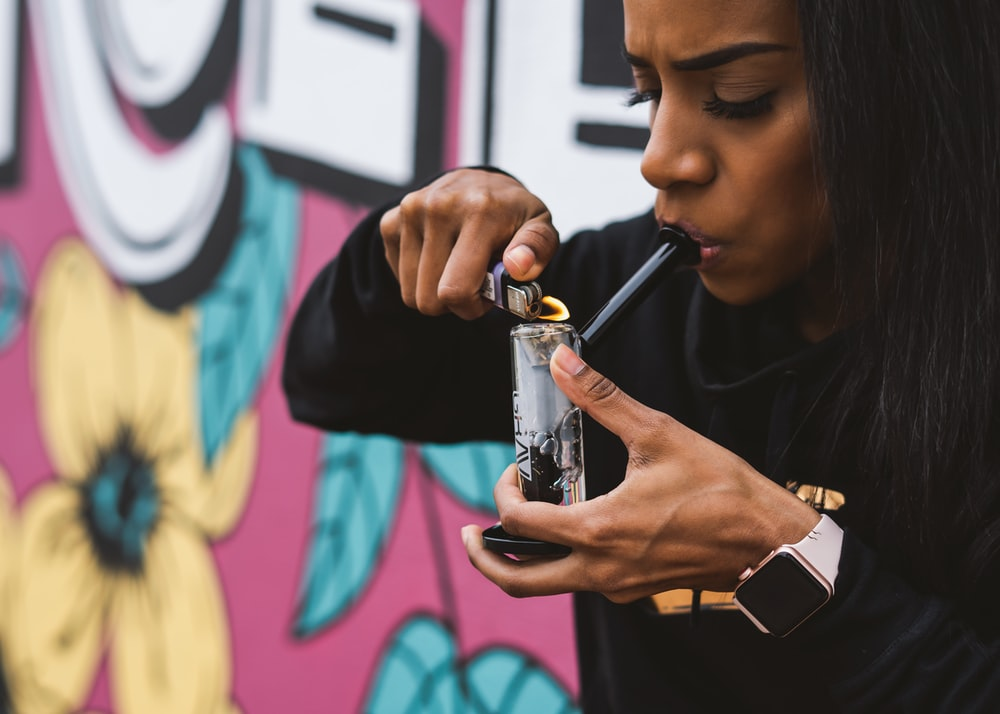 woman holding glass bong