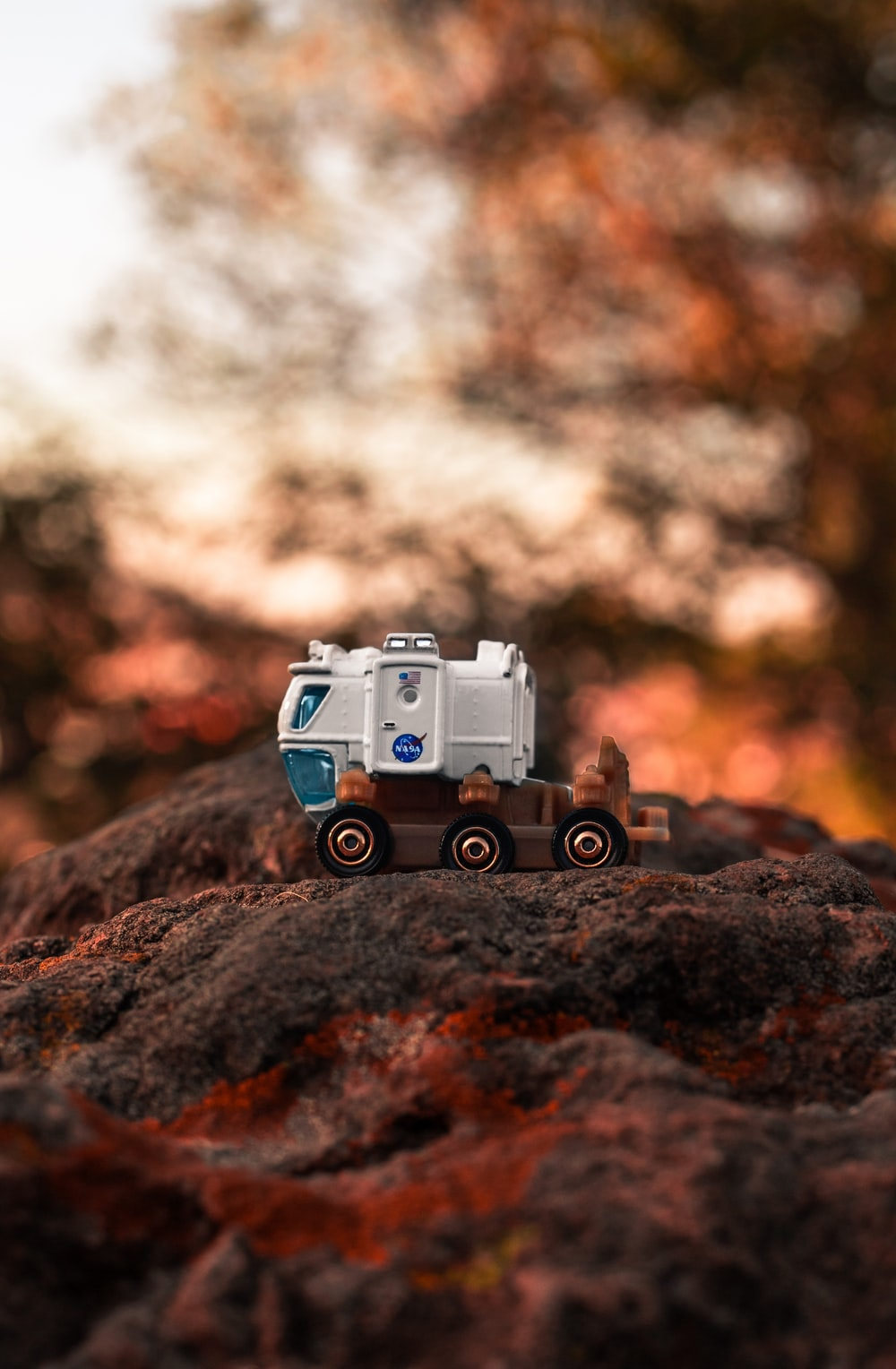 selective focus photography of white and brown truck on rock formation