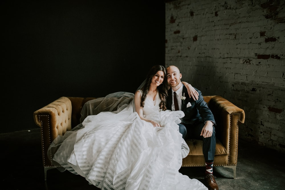 smiling bride and groom sitting on sofa
