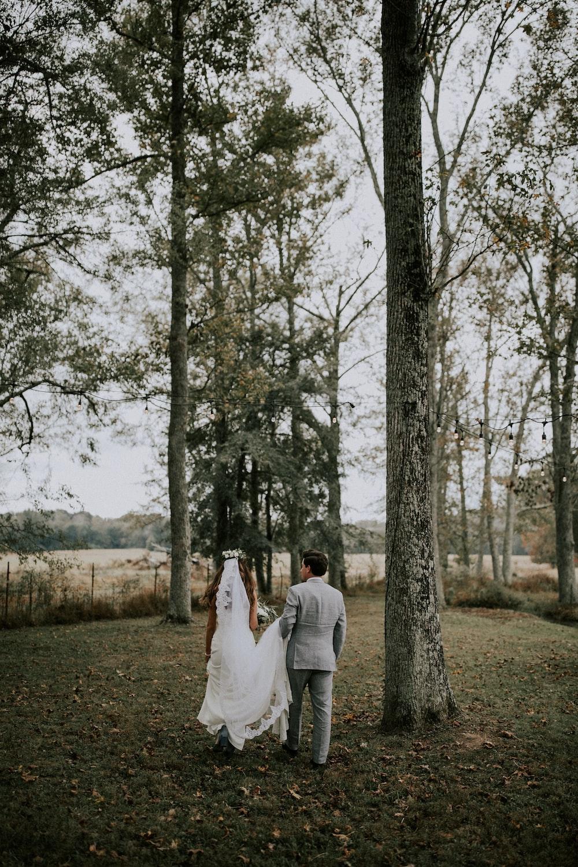 man and woman walking near trees during daytime