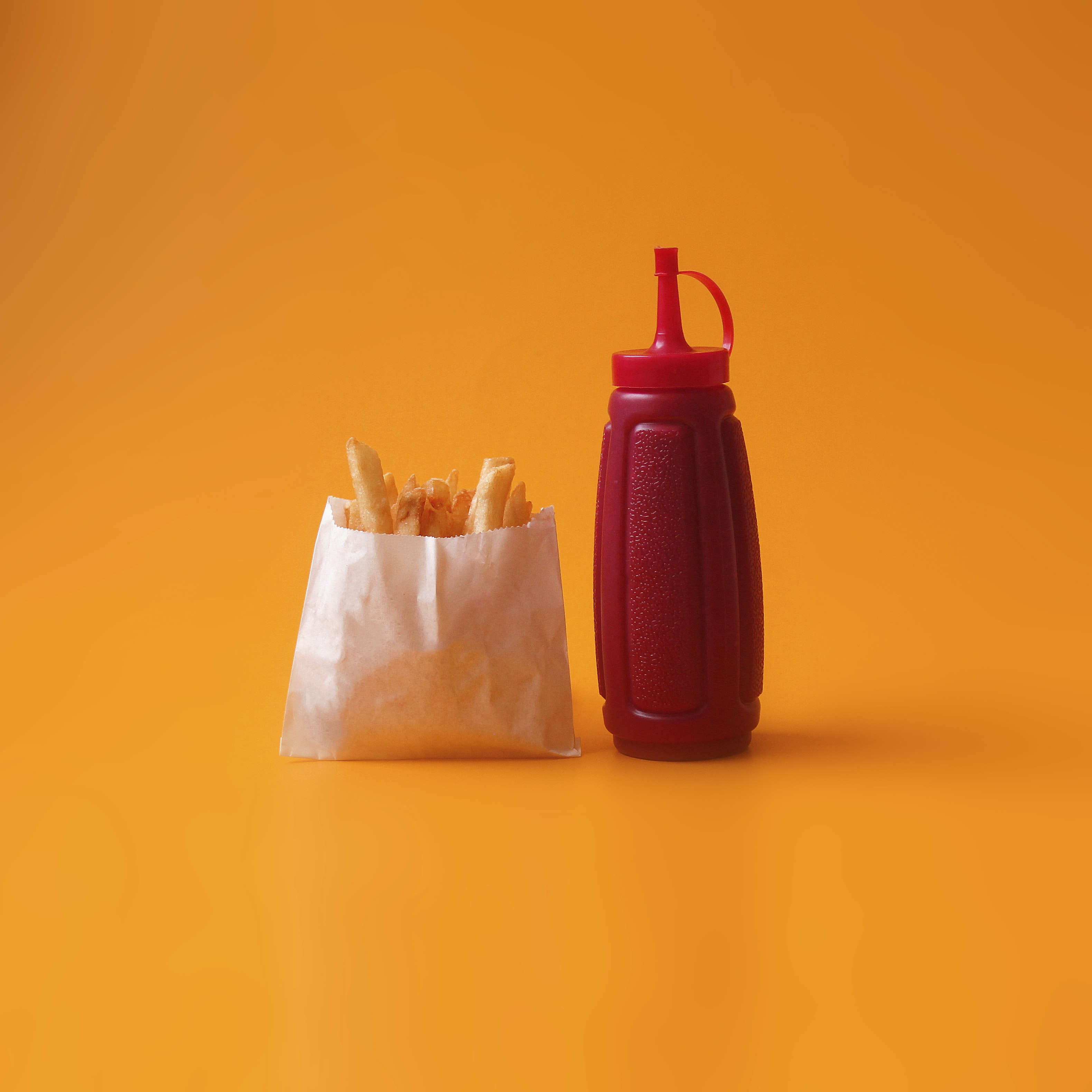 fried fries in white pack beside red squeeze bottle