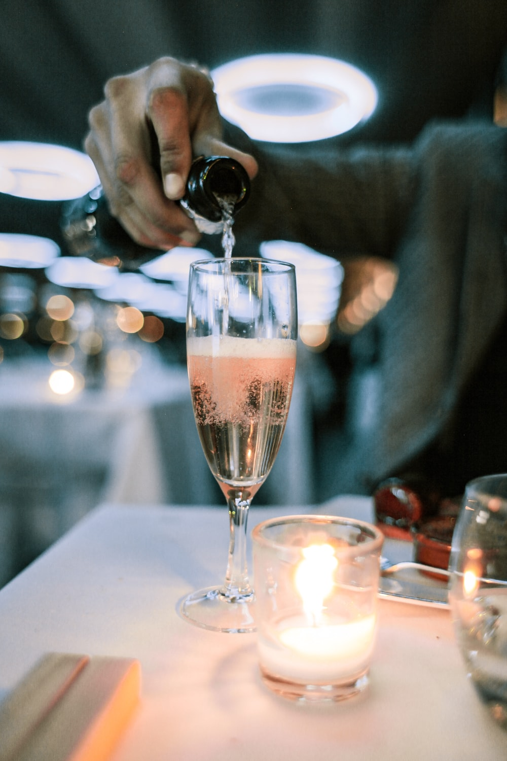 person putting champagne in champagne glass