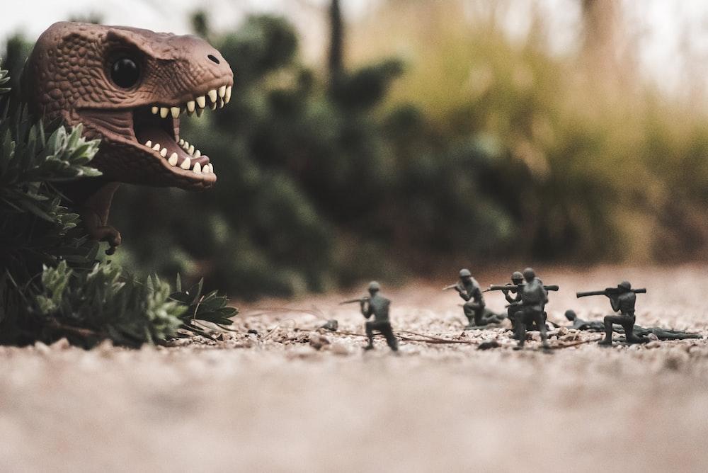 group of soldier near dinosaur miniature