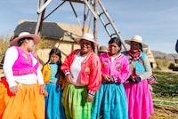 group of women wearing pleated dresses near barn