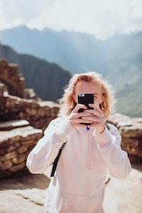 woman wearing white sweater taking selfie