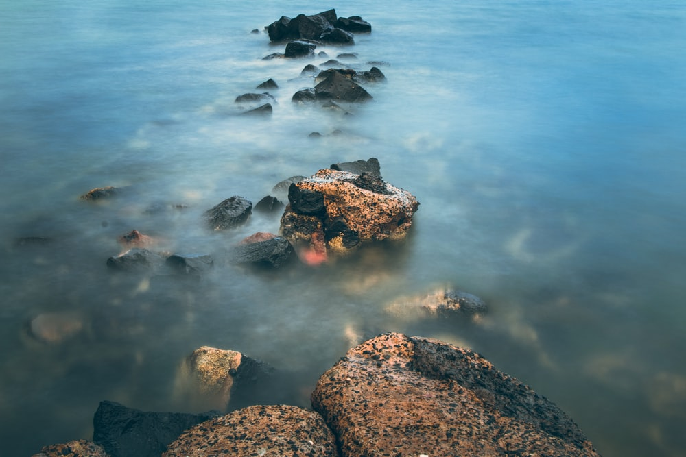 brown rocks in blue water during daytime