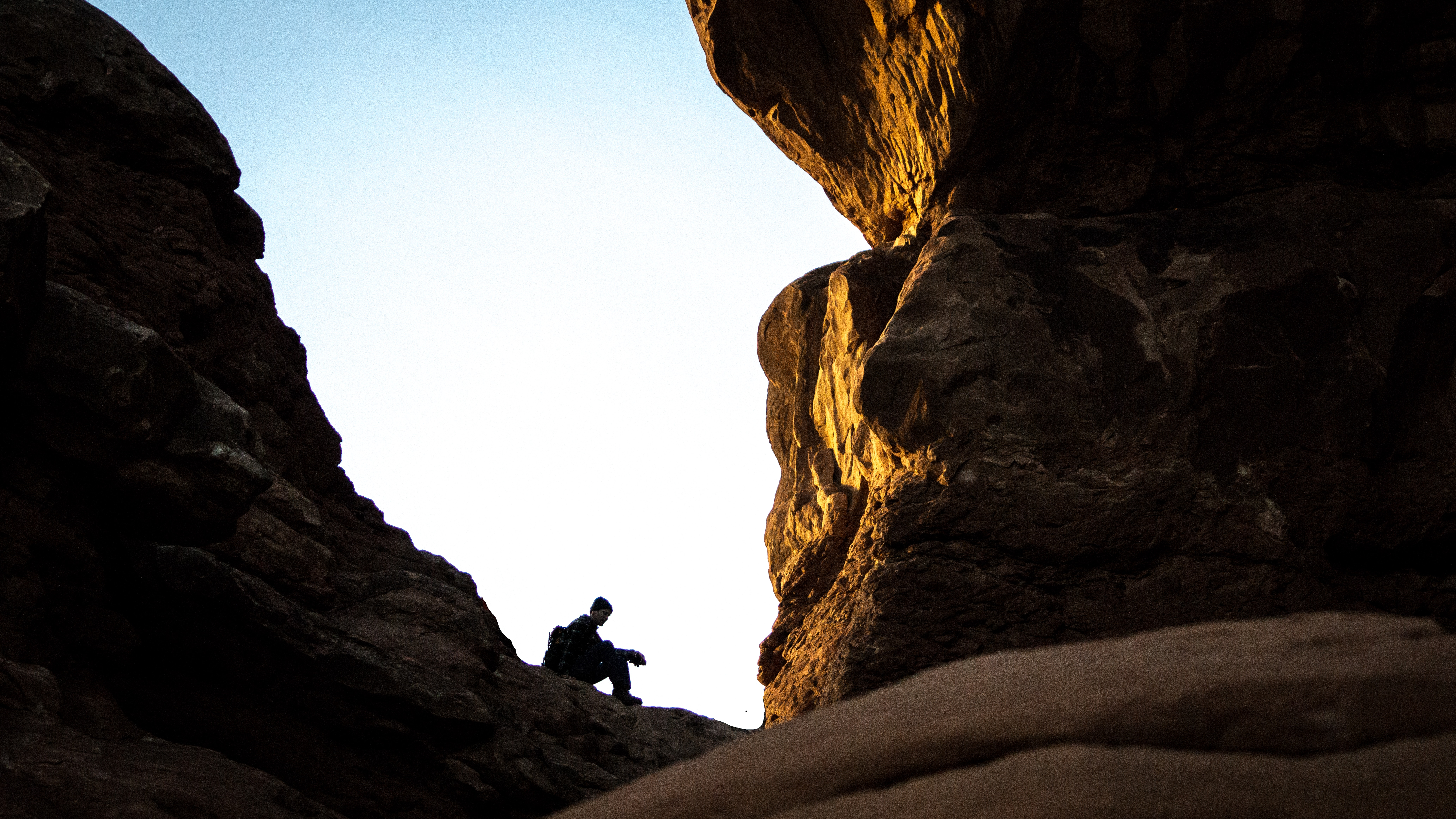 silhouette of person sitting on brown rock