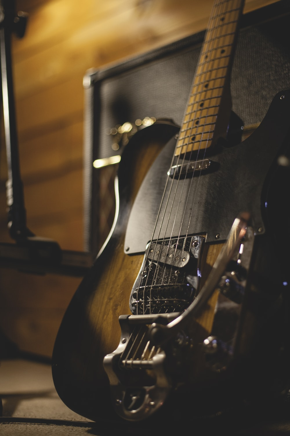 shallow focus photo of black and brown electric guitar